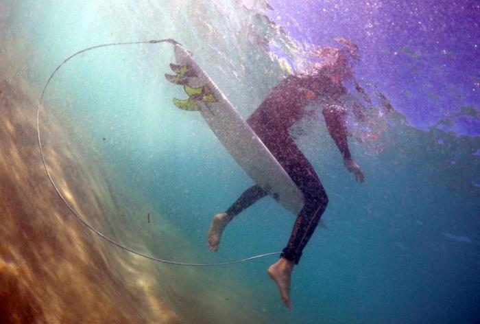 Серфер Арлен Макферсон демонстрирует доску для серфинга, оснащенную электронным отпугивателем акул на пляже Бонди Бич.