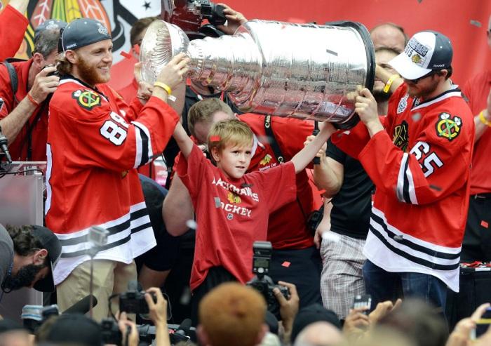 Игроки хоккейной команды «Чикаго Блэкхокс» держат выигранный Кубок Стэнли.