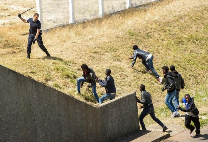 Французский полицейский препятствует нелегальным иммигрантам, пытающимся спрятаться в транспорте, отправляющемся в Великобританию, в Кале.