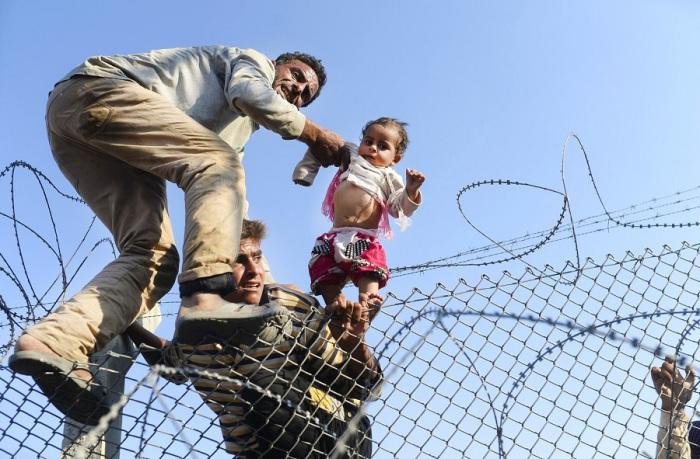 Сирийского ребёнка нелегально переносят через границу Сирии и Турции в город Акчакале провинции Санлыурфа.