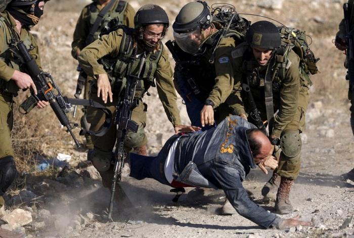 Израильские солдаты задерживают палестинского протестующего во время столкновений после протеста против строительства еврейских поселений в лагере беженцев Аль-Джалазун рядом с Рамаллой.