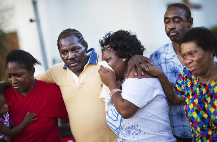 Сын и внучка Этель Ланса, которая погибла во время стрельбы в Чарльстоне, отходят от мемориала перед африканской методистской епископальной церковью в сопровождении членов семьи.