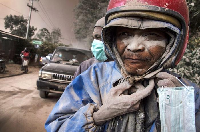 Лица водителя и пассажира мотоцикла покрыты пеплом вулкана Синабунг.