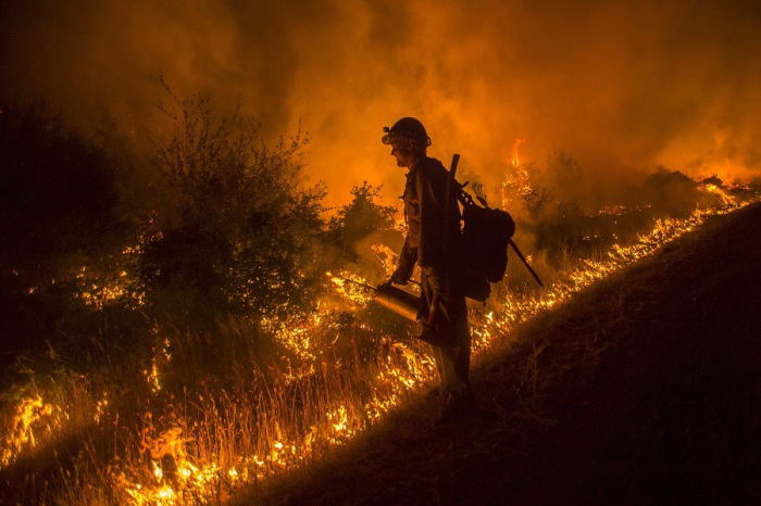 Пожарный борется с неконтролируемым пожаром, который разразился в лесу в Северной Калифорнии из-за ужасной летней засухи.