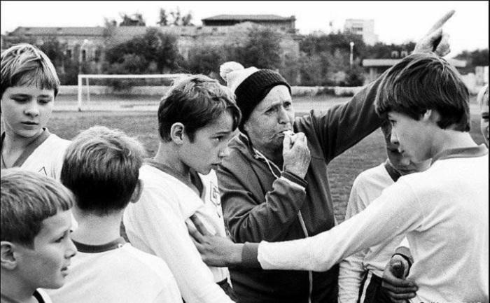 Тренер с помощью свистка и взгляда разнимает ребят футбольной команды.