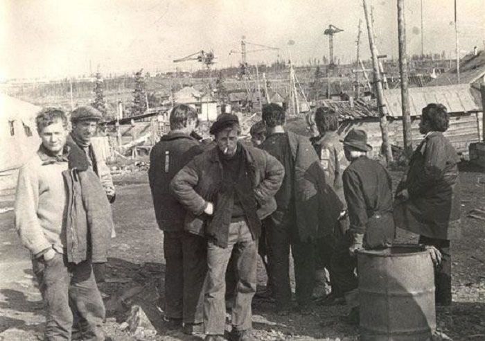 Группа мужчин стоит и обозревает предстоящую работу.
