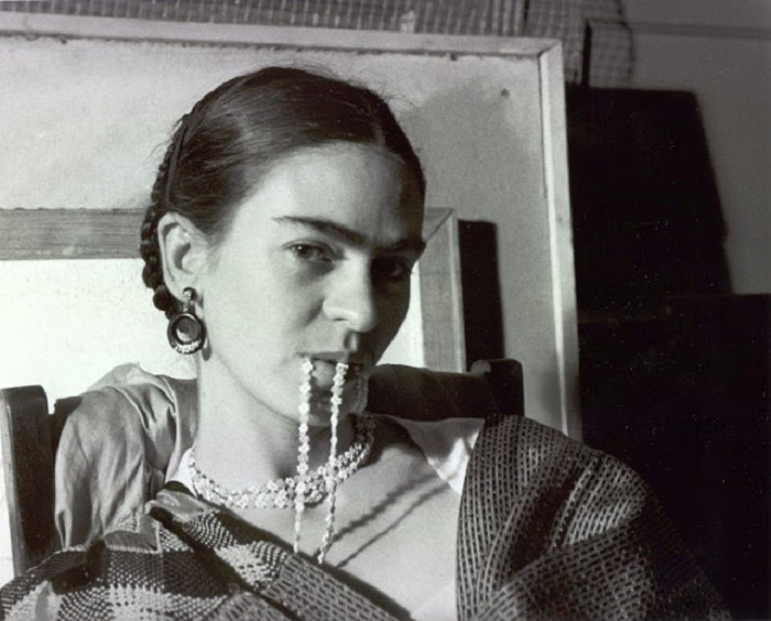 Фрида позирует подруге в нью-йоркской студии с зажатым между губами ожерельем.