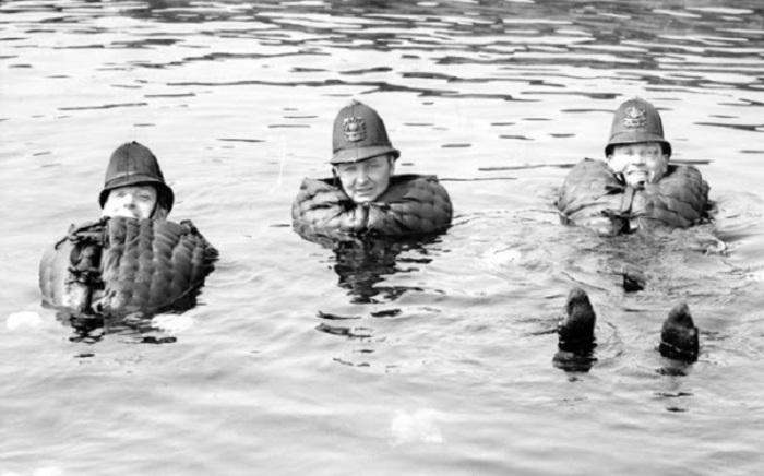 Трое полицейских проводят тест-драйв спасательных жилетов в доках Вест-Индии.