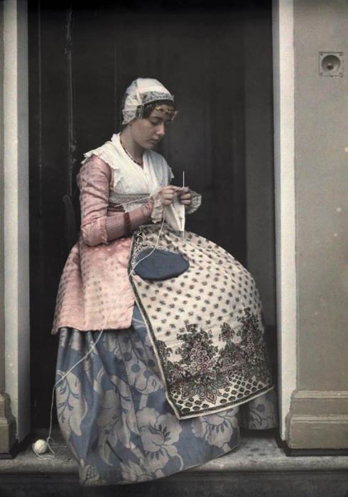 Молодая женщина в национальной одежде вяжет в Коог-ан-де-Заан.