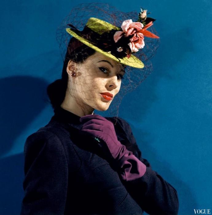 Модель в фетровой шляпе с вуалью и розами, и сиреневых перчатках, Vogue 1941 года.