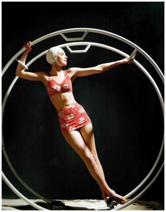 Модель в купальном костюме с цветочным принтом стоящая внутри тренировочного кольца.