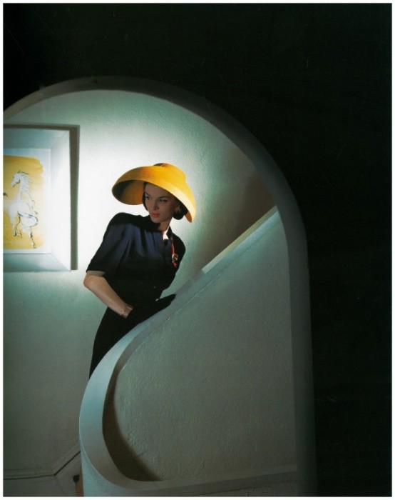 Модель в темном платье, сочетающемся с контрастной ярко-желтой шляпкой.