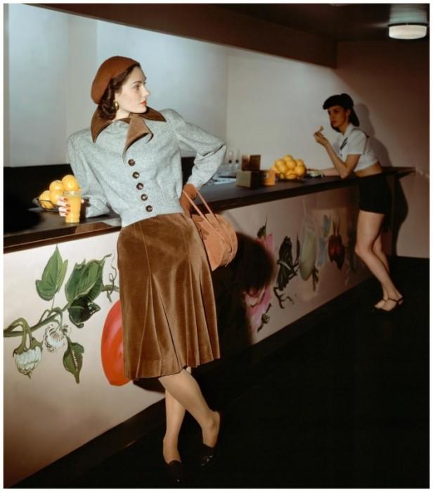 Модель в серо-коричневом твидовом костюме, пиджак которого имеет популярные в то время широкие плечи.