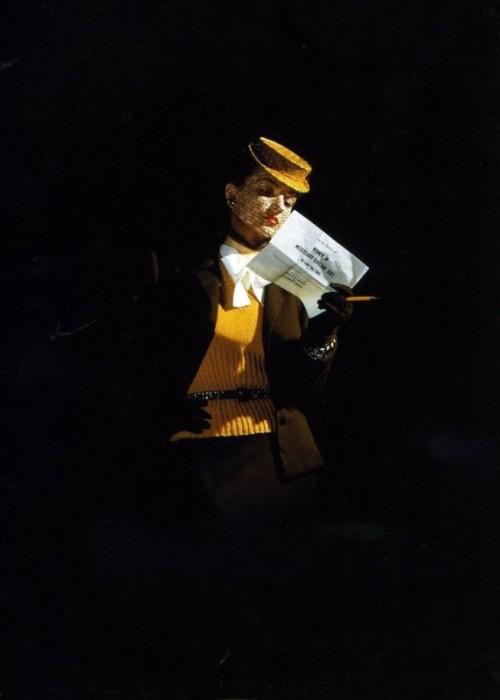 Модель в желтой шляпке с вуалью и свитере, декорированном широким бантом.