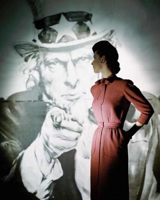 Модель в узком клетчатом платье с карманами на фоне плаката с дядей Сэмом.