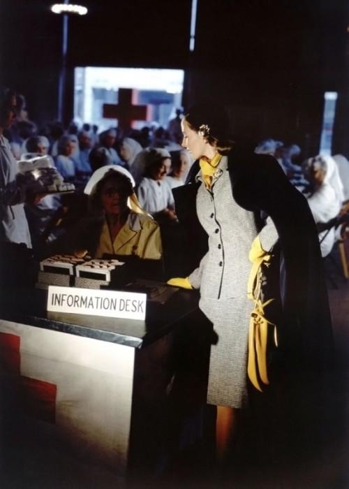 Модель в сером костюме, дополненном яркими аксессуарами – шарфом, перчаткам и сумочкой.