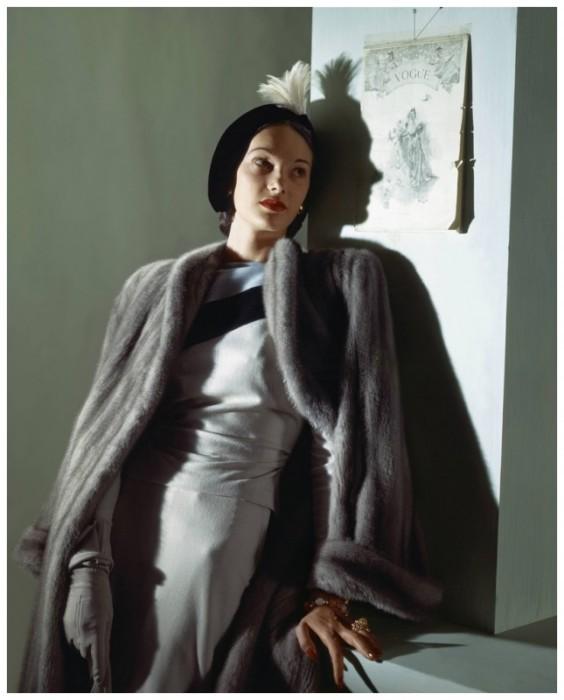 Модель в богатой норковой шубе и элегантной черной шляпке, декорированной перьями.