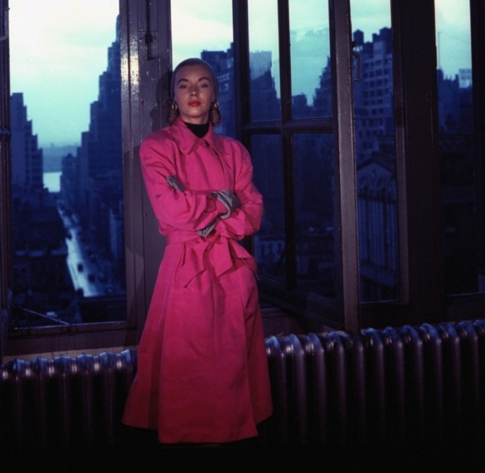Модель в ярко-розовом плаще на фоне окна, выходящего на Манхэттен.