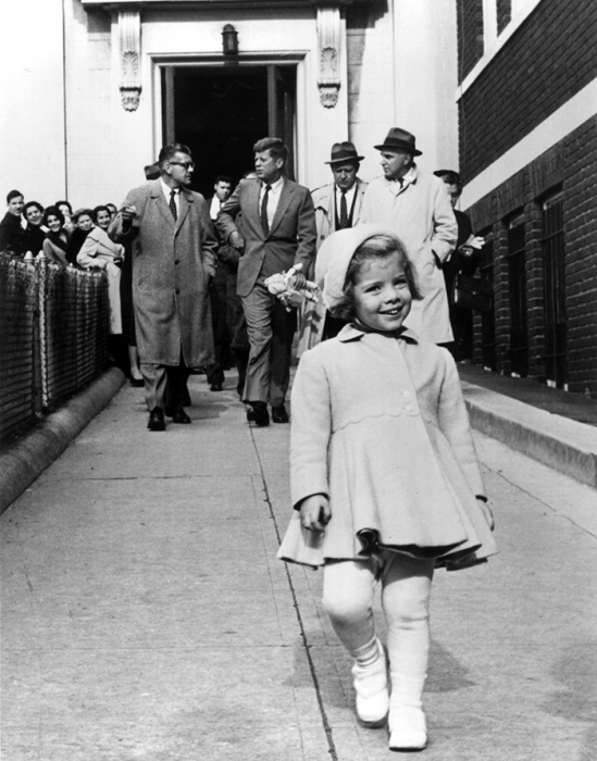 Каролина Кеннеди бежит впереди папы, который несет ее куклу, 1963 год.