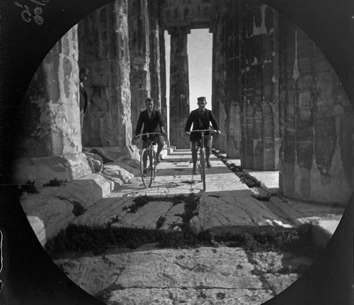 Уильям и Том на велосипедах у колоннады Парфенона.