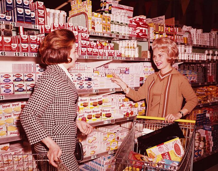 Две женщины выбирают товар, разложенный на полках. 1970 год.