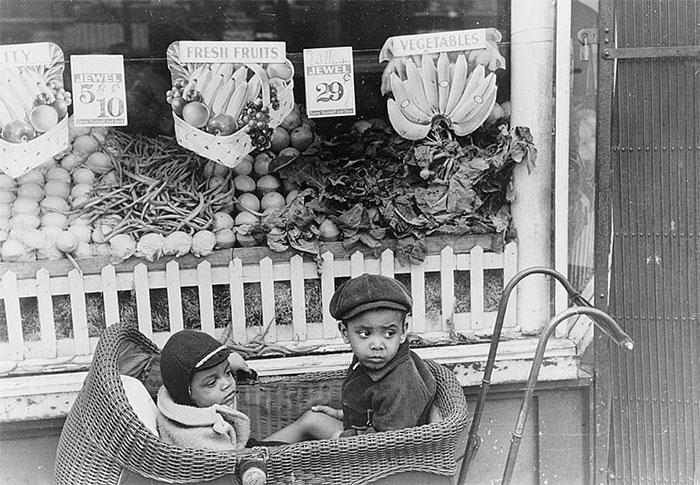 Дети перед магазином, который предлагает покупателям овощи и фрукты. Чикаго, Иллинойс, 1941 год.