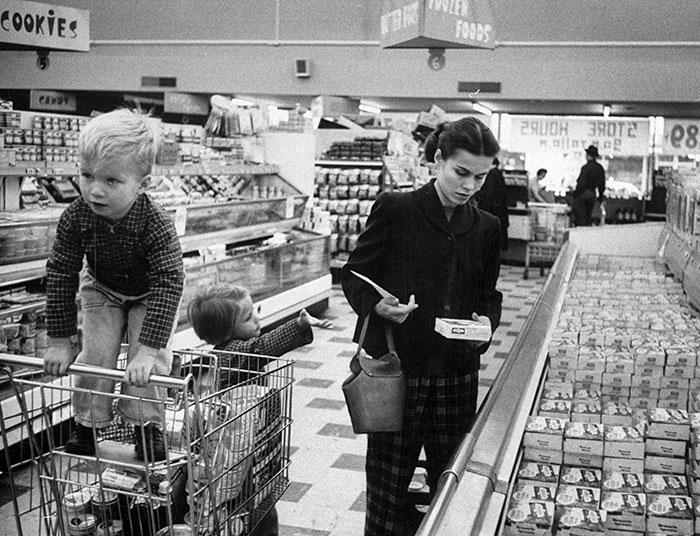 Молодая мама с двумя детьми покупает продукты. 1956 год.