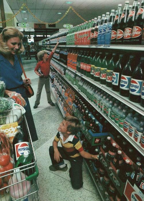 На полке стоят бутылки безалкогольных напитков в таре из стекла. 1980 год.