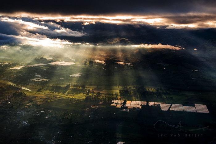 Солнечные лучи, падающие на землю, сквозь грозные, свинцовые тучи.