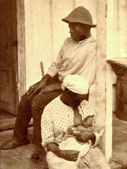 После трудной работы уставшая женщина кормит малыша на крылечке.