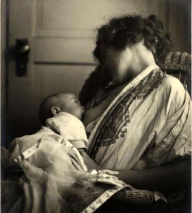 Младенец из под груди смотрит на спящую маму.