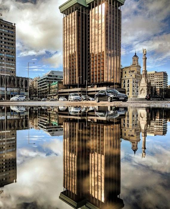 Восхитительные небоскребы испанской столицы через отражение в лужах – завораживают и пленят.
