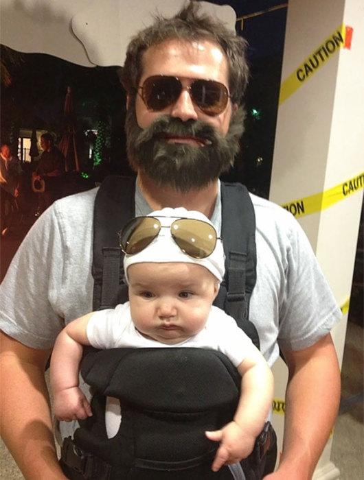 Младенец и его отец переодеты на праздник Всех святых в оригинальные костюмы.