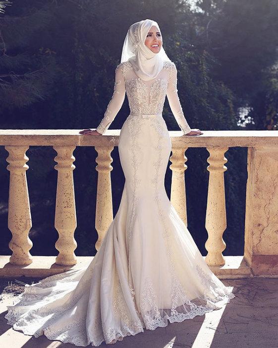 Спускающийся до пола и стелящийся по его поверхности шлейф белого платья.