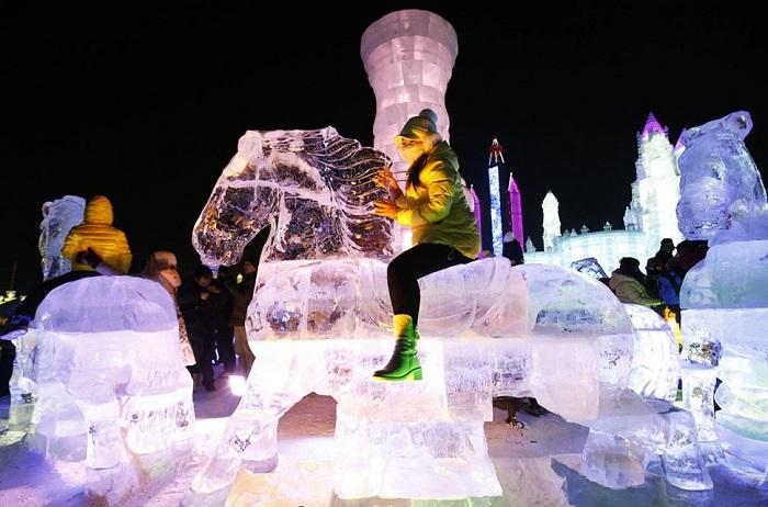 Дети «катаются» на ледяной скульптуре.