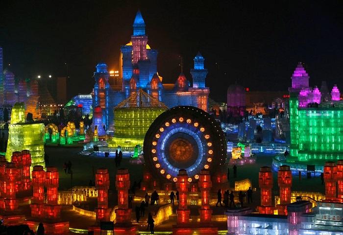 Посетители любуются ледяными скульптурами, освещёнными огнями.