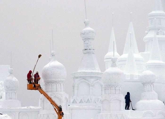 Рабочие полирующие снежную скульптуру.