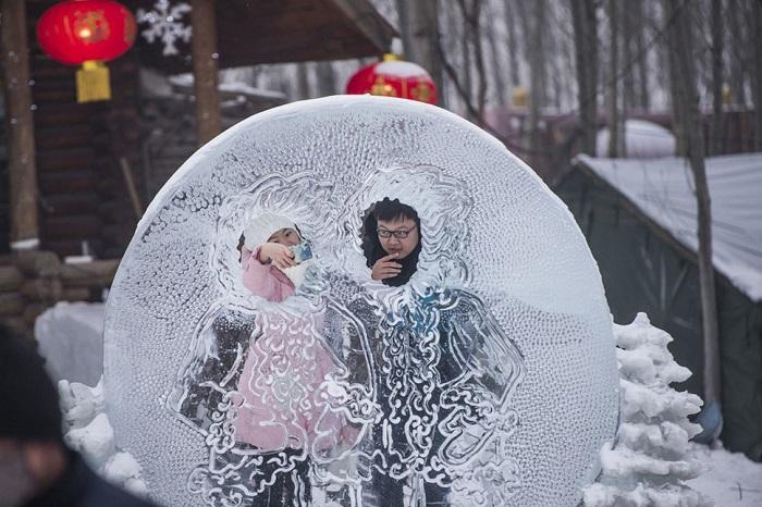 Влюблённые фотографируются в ледяной скульптуре.