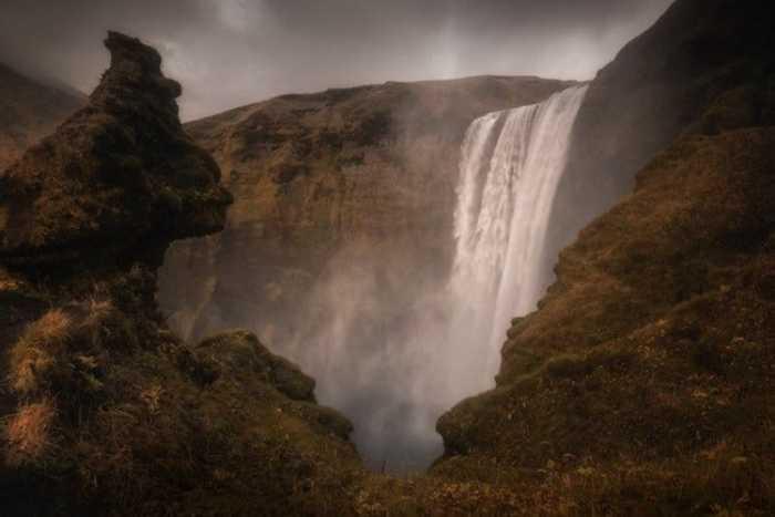 Бурные потоки воды стремительно бегут вниз, рассыпаются на тысячи брызг и зависают в воздухе.