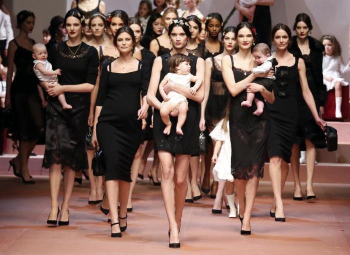 Модели презентовали коллекцию одежды с детьми на руках.