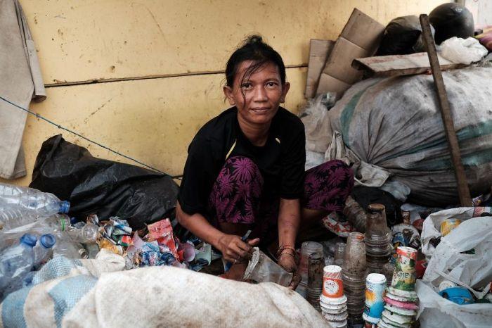 Молодая женщина собирает мусор из пластика, сортирует его и отдает на переработку.