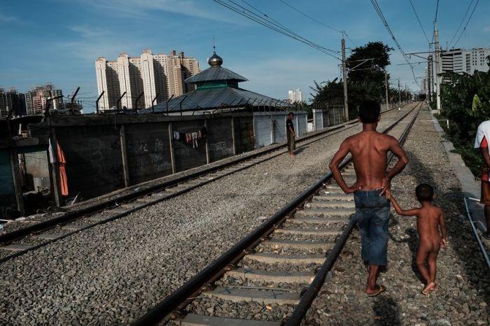 Отец с сыном прогуливаются вдоль действующей железной дороги.