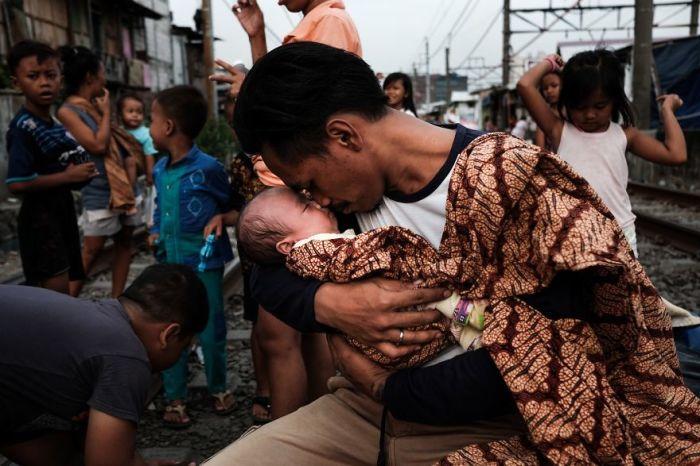 Джонатан обнимает свою маленькую дочь после тяжелого трудового дня.