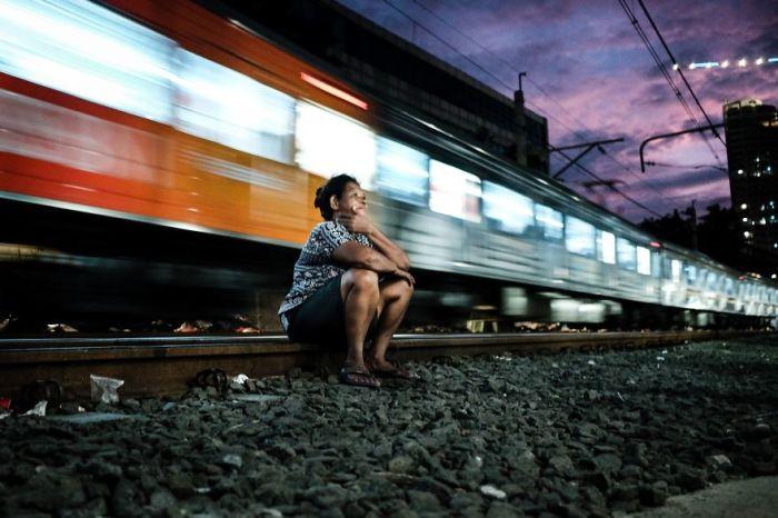 Женщина отдыхает на рельсах под стук проносящегося позади нее поезда.