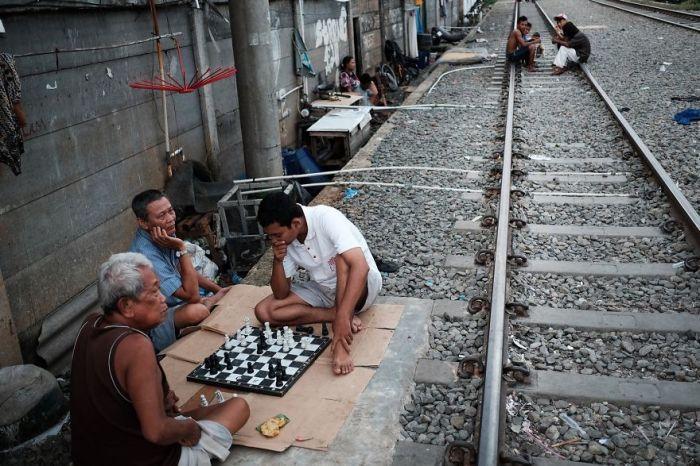 Мужчины играют в шахматы вблизи с железнодорожными путями.
