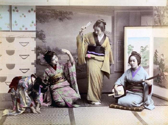Юные особы под руководством учительницы осваивают азы пения и игре на японской лютне.