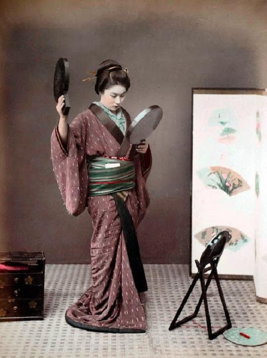 Девушка пытается рассмотреть прическу с помощью зеркал, которую сделала сама.