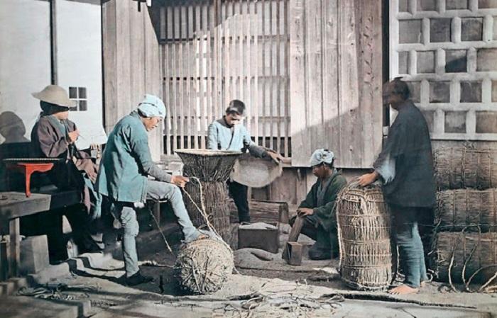 Рабочие закатывают рисовые тюки для продажи.