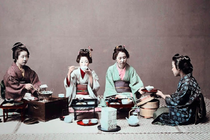 Девочки-служанки прислуживают гейшам за столом.