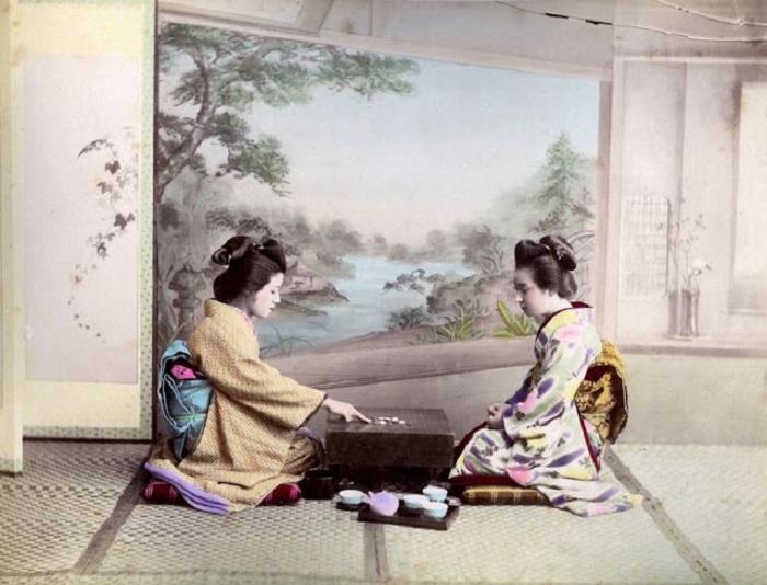 Две девушки в кимоно играют в настольную игру.
